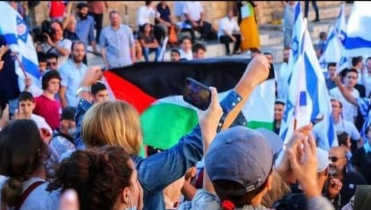 """من هي السيدة التي رفعت علم فلسطين وسط """"مسيرة الأعلام"""" في القدس المحتلة؟"""